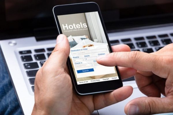 Close-up Of A Man's Hand Booking Hotel Using Smartphone